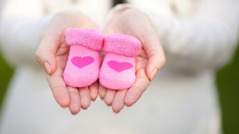 Młoda kobieta trzyma różowe buciki dla noworodka.