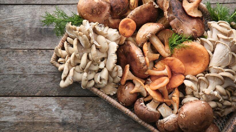 Na drewnianym blacie leżą grzyby.