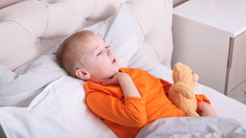 Chłopczyk leży w łóżku i cierpi z powodu chrypki.