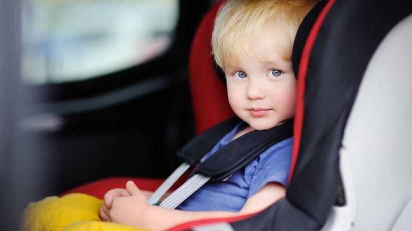 Mały chłopczyk siedzi w foteliku samochodowym. Jest przypięty pasami bezpieczeństwa.