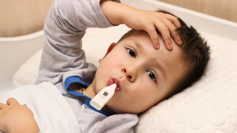 Mały chłopczyk leży w łóżku i trzyma termometr w buzi.