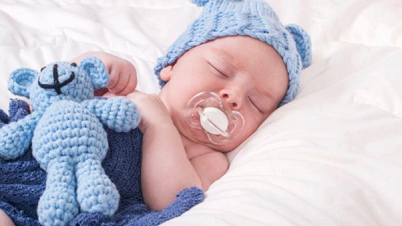 Na łóżku śpi niemowlak. Na główce ma niebieską czapeczkę,