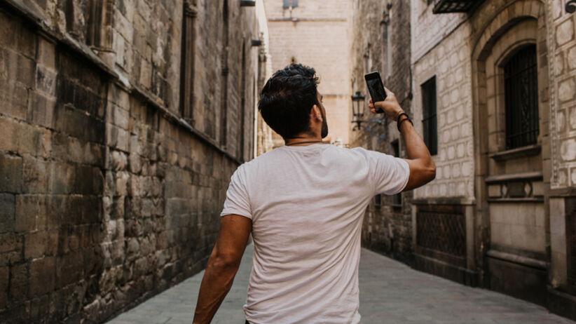 Młody mężczyzna w białej koszulce odwrócony tyłem idzie przed siebie i robi sobie selfie telefonem