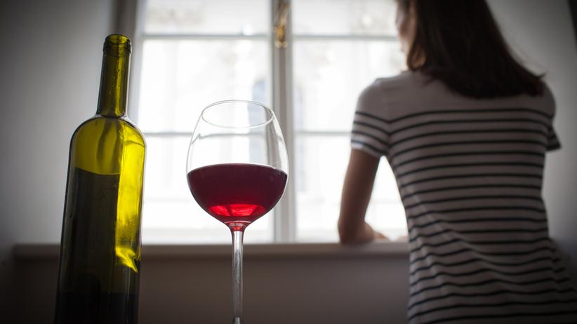 kobieta spoglądająca przez okno, wino na stole