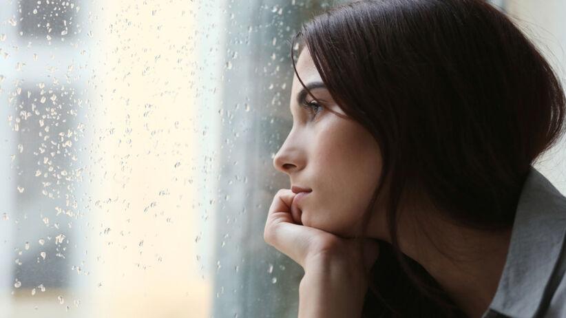 Zasmucona kobieta wygląda przez okno, za którym pada deszcz