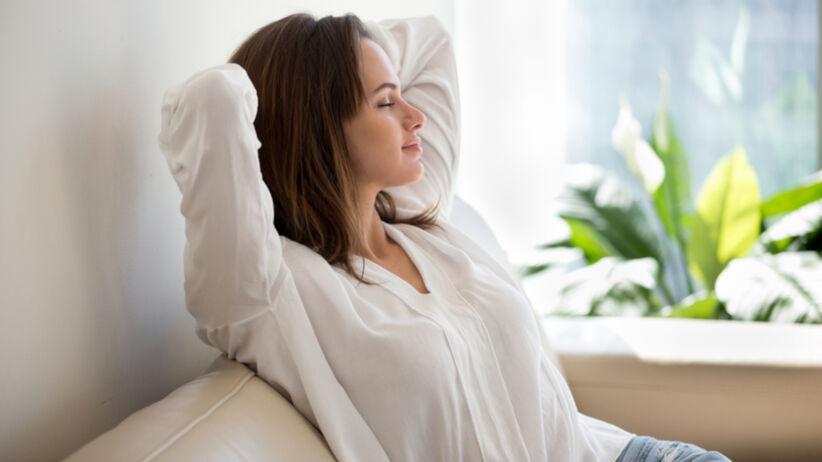 Młoda kobieta próbuje odpocząć na kanapie