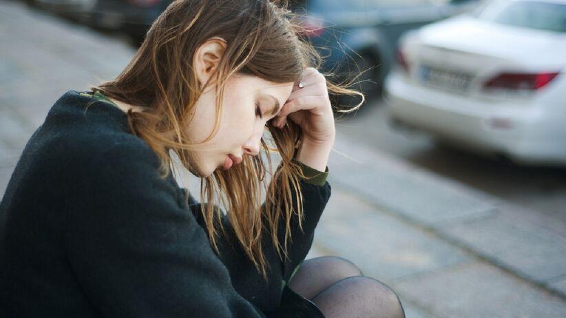 Smutna kobieta w czerni siedzi załamana na ulicy