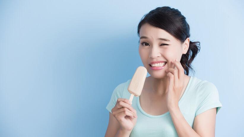 Nadwrażliwość zębów objawia się m.in. bólem po zetknięciu zębów z czymś zimnym, gorącym lub kwaśnym