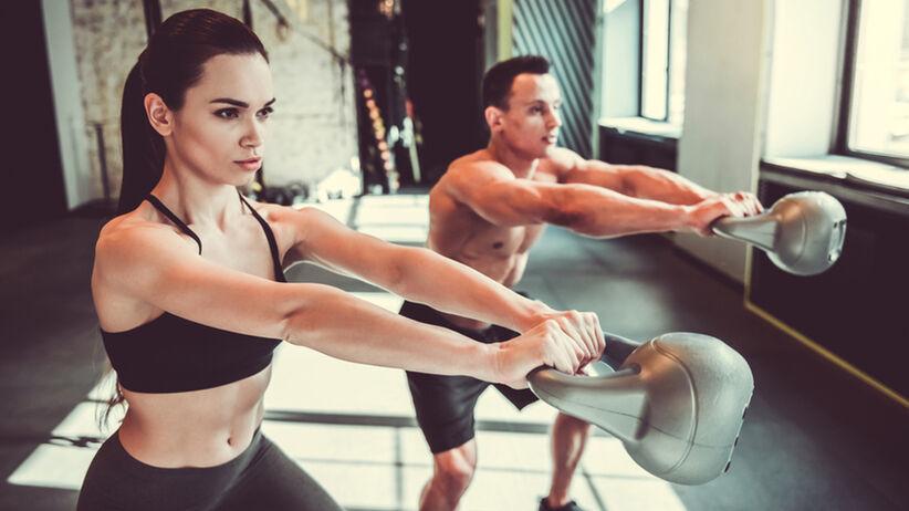 Kobieta i mężczyzna ćwiczą tricepsy na siłowni z kettlebellem