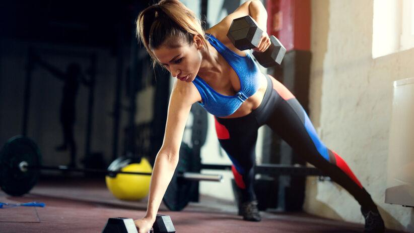 Dziewczyna na siłowni wykonuje ćwiczenia z hantlami