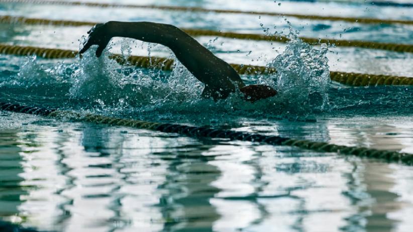 Młody mężczyzna pływa na basenie